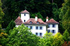 Small mansion in Switzerland. In some green trees Royalty Free Stock Images