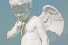 A small marble Cupid brings his finger to his lips Royalty Free Stock Photo