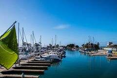 Small marina with beep blue water and many sail and power boats docked in slips. Small marina with beep blue water and many sail and power boats docked in slips stock image