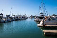 Small marina with deep blue water and many sail and power boats docked in slips. Small marina with deep blue water and many sail and power boats docked in slips royalty free stock photo