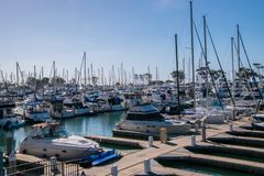 Small marina with deep blue water and many sail and power boats docked in slips. Small marina with deep blue water and many sail and power boats docked in slips royalty free stock image