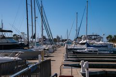 Small marina with deep blue water and many sail and power boats docked in slips. stock image