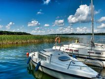 Small Marina in Kietlice in northern Poland. Marina in Kietlice over Mamry lake in Masuria region in northern and. Two boats moored under the summer, blue sky stock photo
