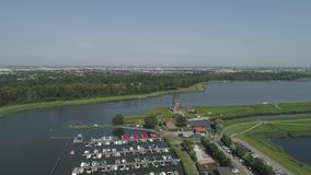 Small marina wit a sunny sky and a old Dutch traditional windmill located at Rottemeren lake near Rotterdam