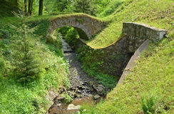 A small medieval stone bridge over the stream Royalty Free Stock Photography