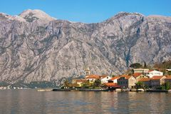Small Mediterranean village with stone houses with red roofs against gray mountains. Montenegro, Bay of Kotor stock photography