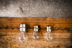Small, medium and large bulbs on the nails on the old wooden Stock Photos