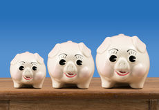 Small medium and large piggy banks on shelf Stock Photos