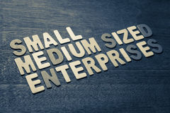 Small and medium sized enterprises. Text on wood background Royalty Free Stock Photos