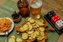 Small melba toast or bruschetta chips on wooden table with beer and sauces royalty free stock images