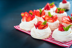 A small meringue Pavlova dessert with some strawberry slices. A small meringue Pavlova dessert with strawberry slices garnished on blue background Stock Photo