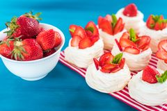A small meringue Pavlova dessert with some strawberry slices with mint leaves on a blue background. A small meringue Pavlova dessert with some strawberry slices Royalty Free Stock Images