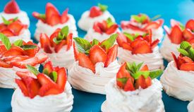 A small meringue Pavlova dessert with some strawberry slices with mint leaves on a blue background. A small meringue Pavlova dessert with some strawberry slices Stock Photos