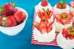 A small meringue Pavlova dessert with some strawberry slices with mint leaves on a blue background. A small meringue Pavlova dessert with some strawberry slices Royalty Free Stock Photos