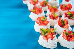A small meringue Pavlova dessert with some strawberry slices. A small meringue Pavlova dessert with strawberry slices garnished on blue background Stock Images