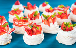 A small meringue Pavlova dessert with some strawberry slices. A small meringue Pavlova dessert with strawberry slices garnished on blue background Stock Photos