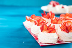 A small meringue Pavlova dessert with some strawberry slices. A small meringue Pavlova dessert with strawberry slices garnished on blue background Royalty Free Stock Image