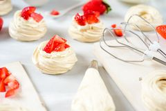 A small meringue Pavlova dessert with some strawberry slices . Top view. pattern. A small meringue Pavlova dessert with some strawberry slices . Top view Royalty Free Stock Image