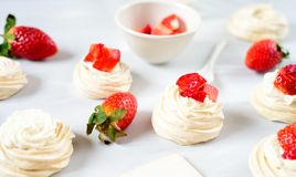 A small meringue Pavlova dessert with some strawberry slices . Top view. Pattern. A small meringue Pavlova dessert with some strawberry slices . Top view Royalty Free Stock Photo