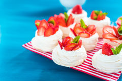 A small meringue Pavlova dessert with some strawberry slices. A small meringue Pavlova dessert with strawberry slices garnished on blue background Royalty Free Stock Photos