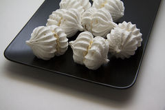 Small meringues on black plate Stock Photo