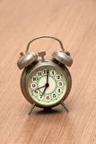 Small Metal Alarm Clock. On the Wood Surface Royalty Free Stock Photography