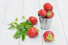 Small metal bucket filled with strawberries and a sprig of mint.  Royalty Free Stock Images