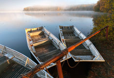 Small metal rowboats on still foggy lake coast Royalty Free Stock Photos