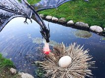 Small metal sculpture of a flying dragon over a nest. Novogrudok, Belarus - May 4, 2018: Small metal sculpture of a flying dragon over a nest Stock Image