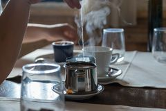 Small metal teapot with tea bag, Some glasses on the restaurant table. White steam rises above hot water..Selective focus royalty free stock photography