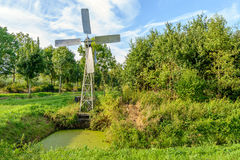 Small metal windmill controls the water level in the ditch. Stock Photography