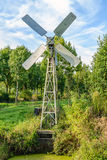 Small metal windmill controls the water level in the ditch. Stock Images