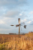 Small metal windmill in a Dutch autumnal landscape Royalty Free Stock Photo