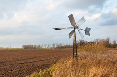 Small metal windmill in a Dutch autumnal landscape Royalty Free Stock Images
