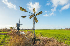 Small metal windmill and a large wooden hollow post mill in a Du. Tch polder landscape on a sunny day in the fall season stock images