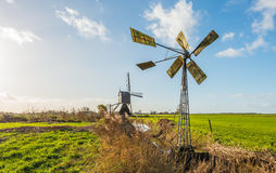 Small metal windmill and a large wooden hollow post mill in a Du. Tch polder landscape on a sunny day in the fall season stock photography
