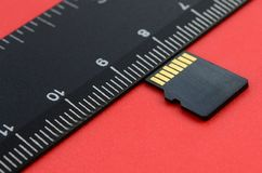 Small micro SD memory card lie on a red background next to a black ruler. A small and compact data and information store Stock Image