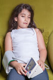 Small middle eastern girl feeling sick bad and holding digital blood pressure device. Royalty Free Stock Image