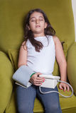 Small middle eastern girl feeling sick bad and holding digital blood pressure device. Stock Photo
