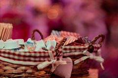Small milk, coffee creamer pots in basket on red blur background. Mono portions, for catering.  royalty free stock image