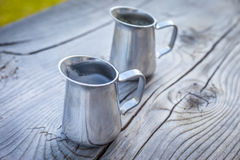 Small milk jug on old wooden table Stock Image