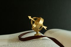Small miniature astrolabe globe on an open book. stock images