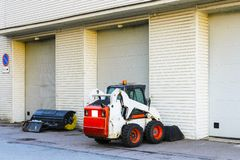small mini tractor with a blade and a bucket for street cleaning is at the gate of a large garage stock photography