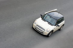 Small minute british car speed. Small minute british car drives rides speed on road on road isolated on gray Royalty Free Stock Photos