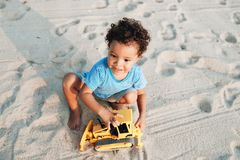 Small Mixed Race Boy Playing with Toy at the beach stock image