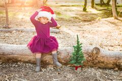 Small Mixed Race Young Baby Girl Having Fun With Santa Hat and a Tree. Cute Mixed Race Young Baby Girl Having Fun With Santa Hat and Christmas Tree Outdoors On royalty free stock photo