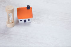 Small model house with a wooden egg timer Royalty Free Stock Photo