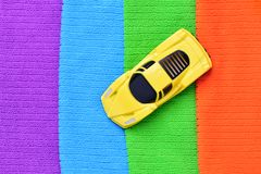 A small model of yellow car stands on colored towels in four colors: purple, blue, green stock photos
