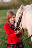 Small model of a young girl child looks at a white horse Royalty Free Stock Photos