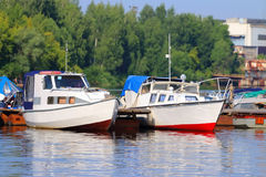 Small modern motorboats at pier on river at summer day Stock Photos